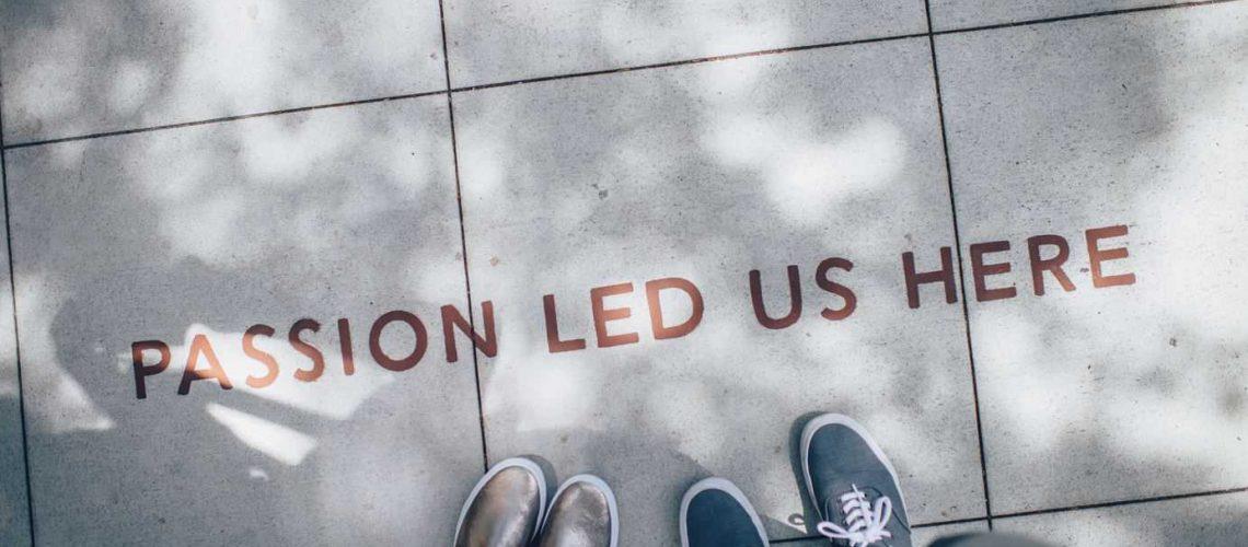 Kaksi ihmistä seisoo jalkakäytävällä, jolla lukee englanniksi
